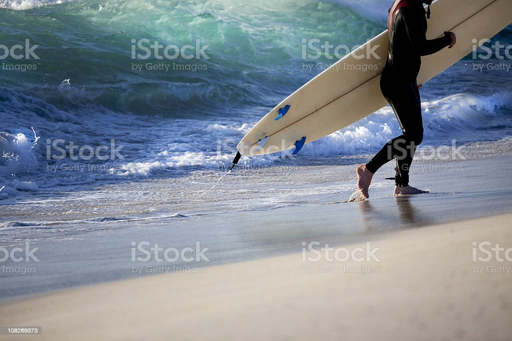 Surfer Walking Along Beach royalty-free stock photo