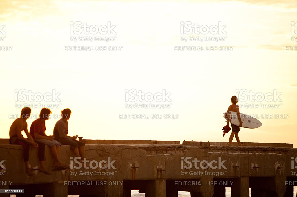 Surfer walking along pier into the Pacific Ocean at sunset stock photo