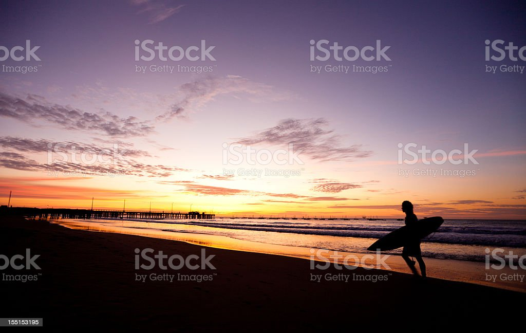 Surfer walking home at sunset stock photo