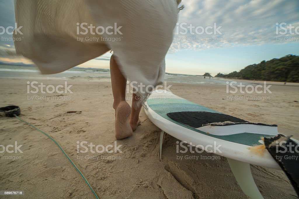 Surfer walking on beach near surfboard stock photo