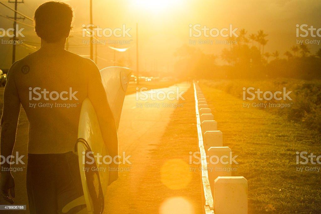 Surfer walking on street in sunset. stock photo