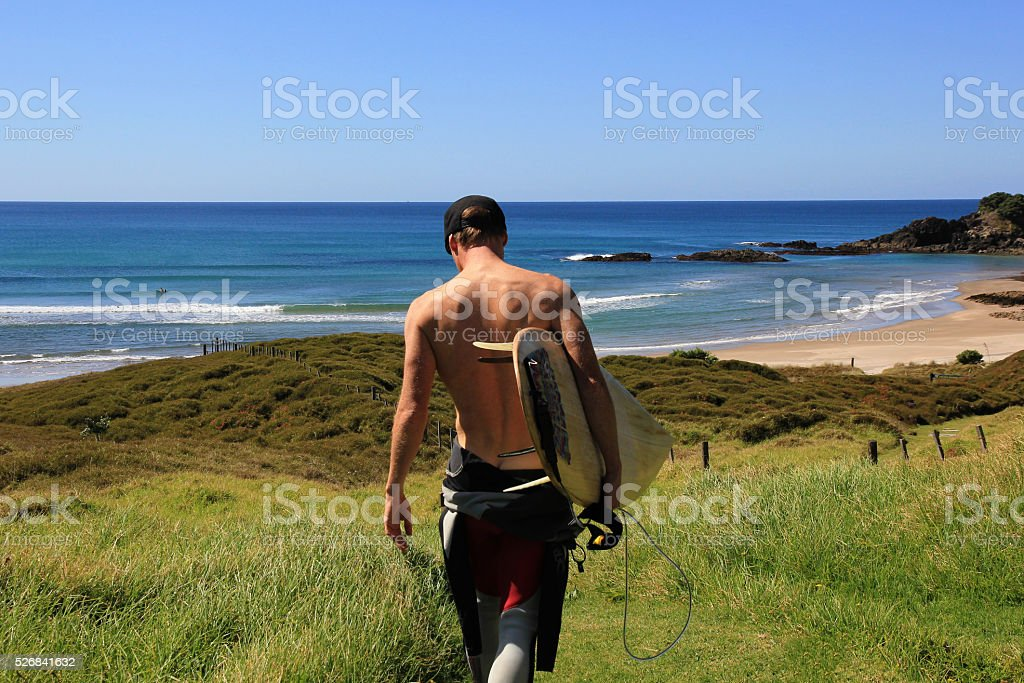 Surfer walking on the beach stock photo
