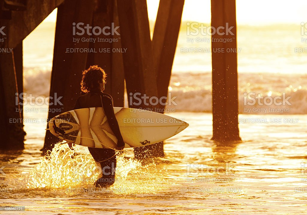 Surfer walking out into the Pacific Ocean at sunset stock photo