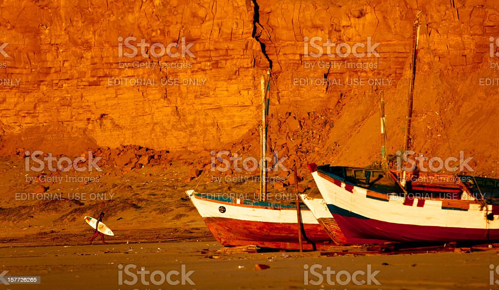Surfer walking past fishing boats at sunset in Peru stock photo