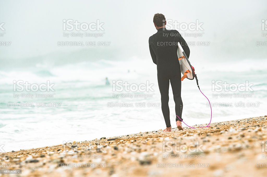 Surfer walking to the sea at Fistral Beach, Newquay stock photo