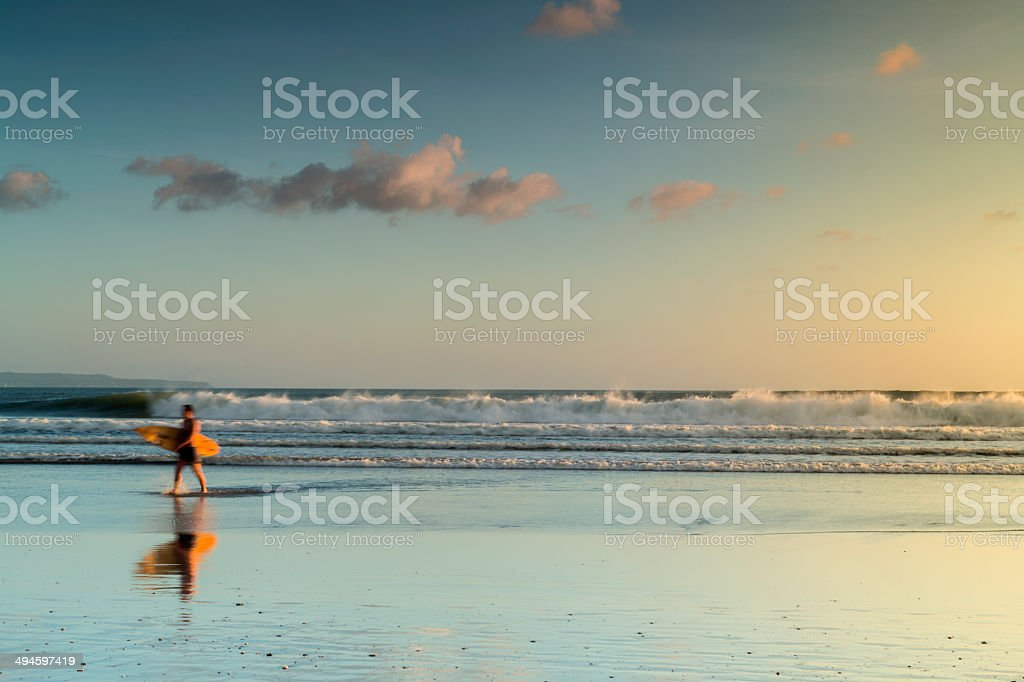 Surfer with board walking on the beach stock photo
