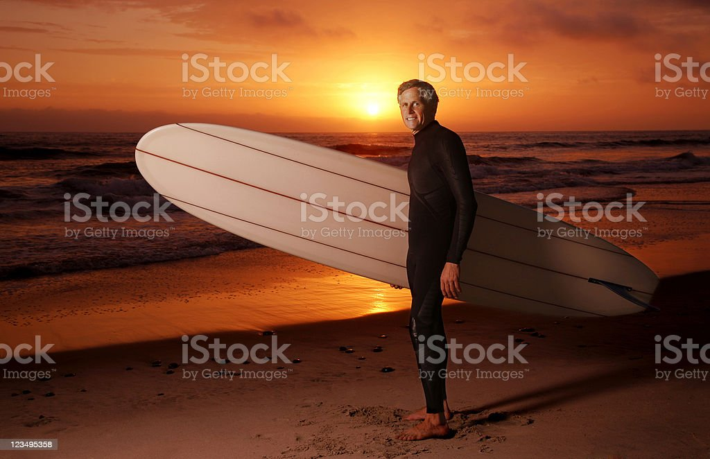 Surfer with Longboard at Sunset stock photo