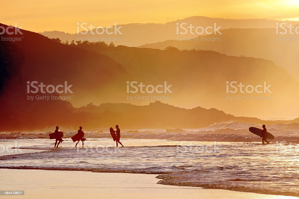 surfers and boogie boards at sunset stock photo