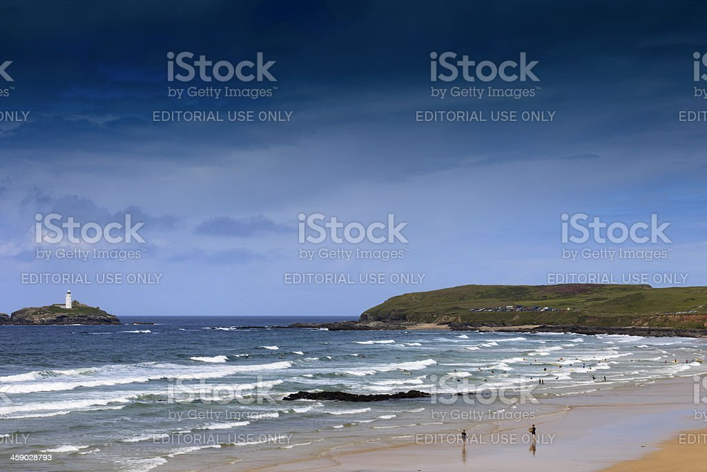 surfers at Gwithian with Godrevy lighthouse in the background stock photo