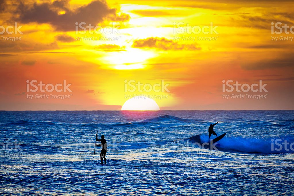 Surfers at Sunset in Poipu Beach of Kauai Hawaii stock photo