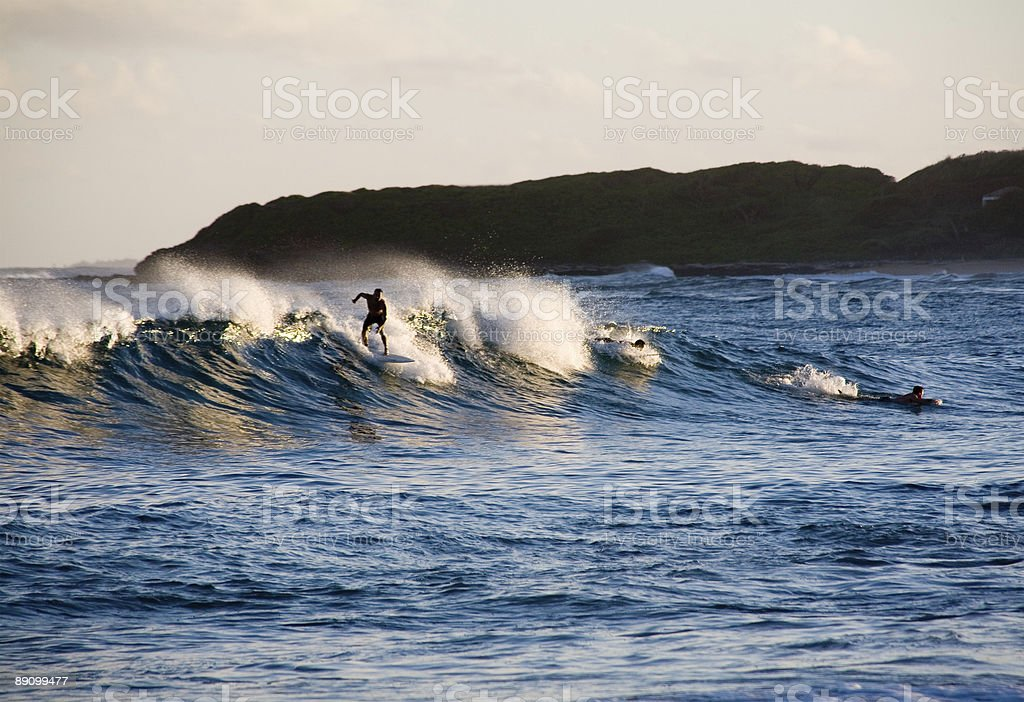Surfers catching the last wave of day royalty-free stock photo
