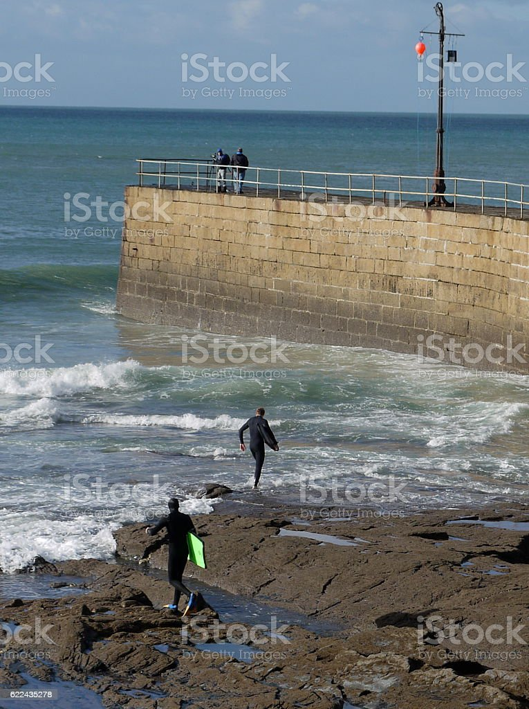 Surfers entering the water near Porthleven pier, Cornwall. stock photo