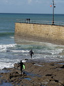 Surfers entering the water near Porthleven pier, Cornwall.