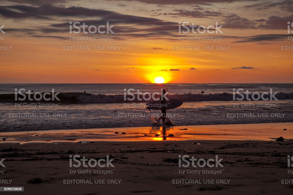 Surfers in Santa Teresa at sunset / Costa Rica stock photo