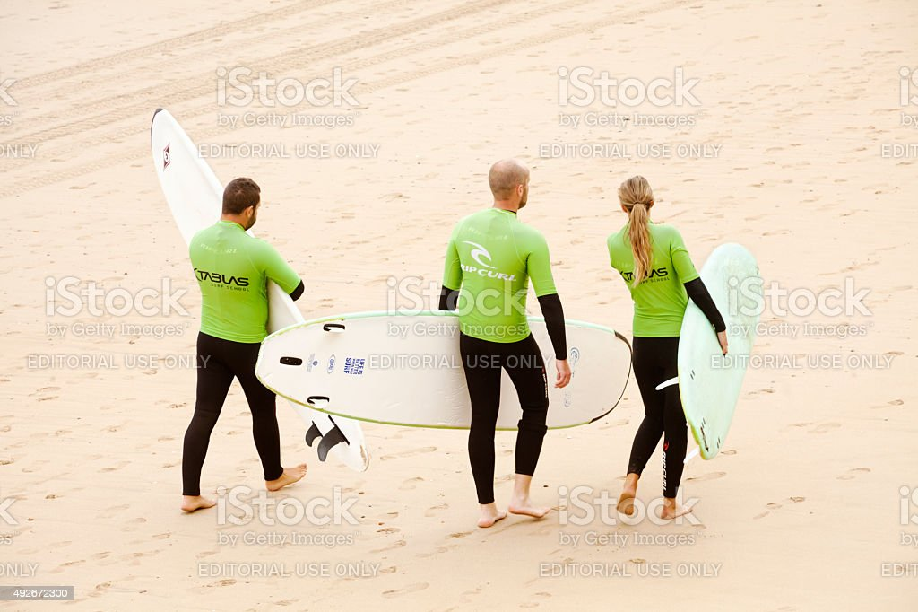 Surfers on the beach carrying surfboards. stock photo