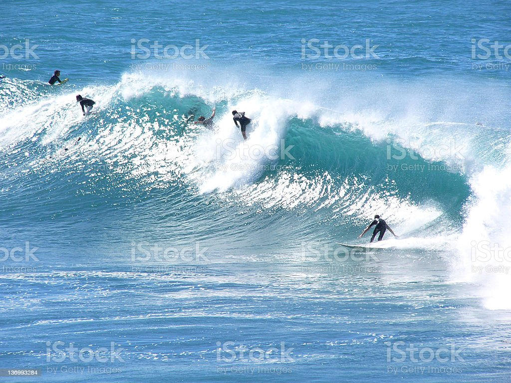 surfers riding big waves stock photo