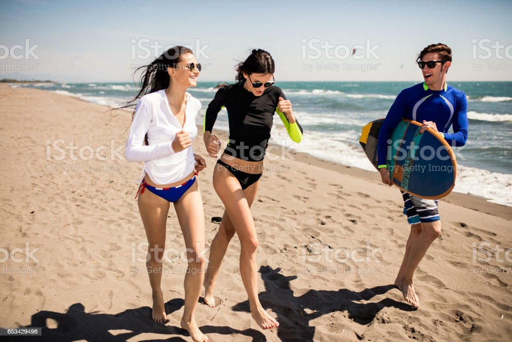 Surfers running to the ocean. Happy friends with surfboard stock photo