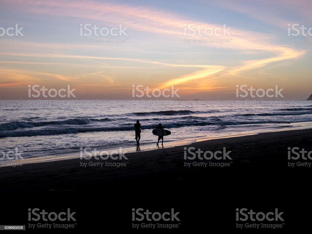 Surfers walks along the beach royalty-free stock photo