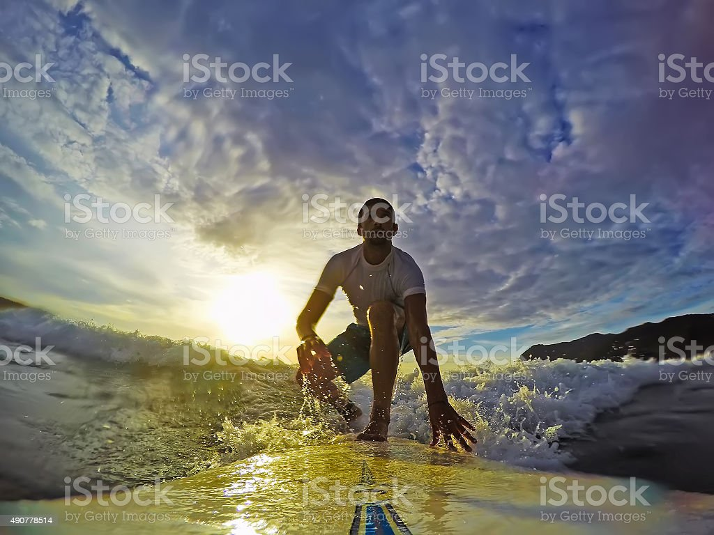 surfing at sunset under clouds stock photo