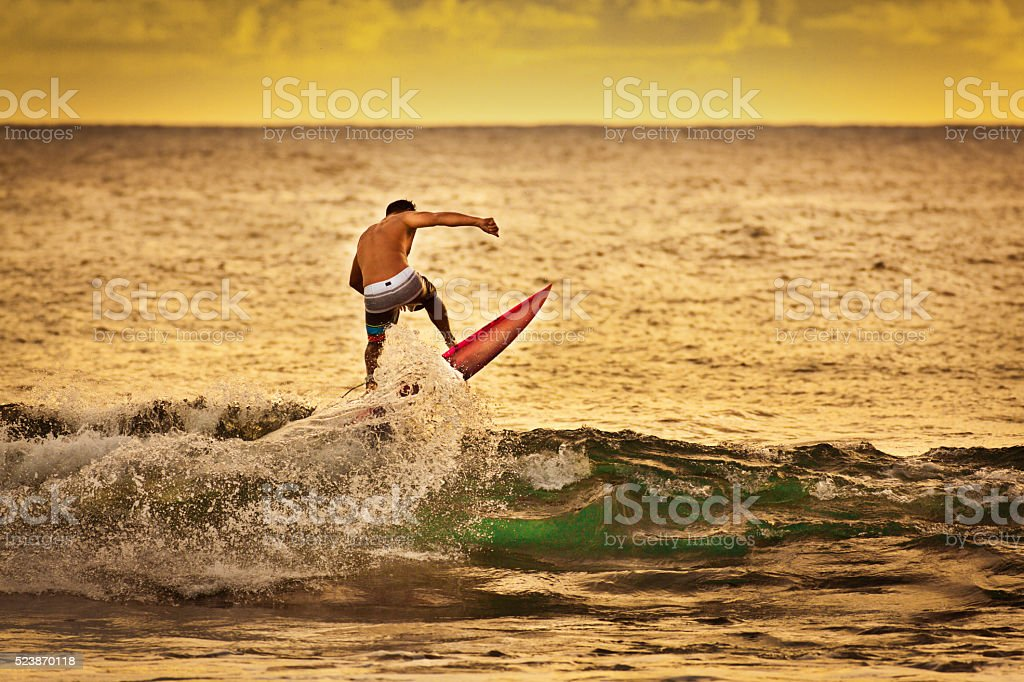 Surfing in Kauai Hawaii at Sunset stock photo