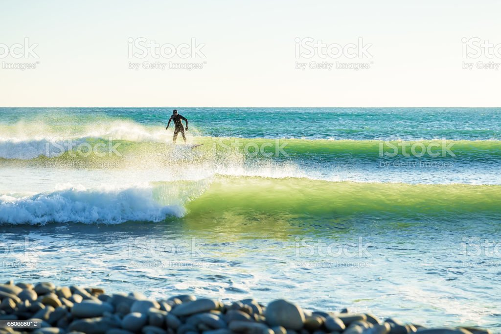 Surfing in ocean. Clear green waves and surfer on wave stock photo