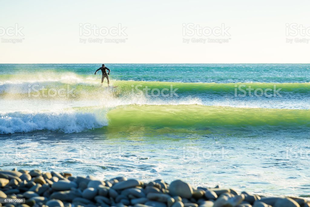 Surfing in ocean. Clear waves and surfer on wave stock photo