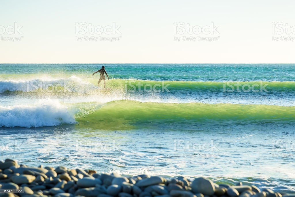 Surfing in the spring. Clear lite waves and surfer in ocean stock photo