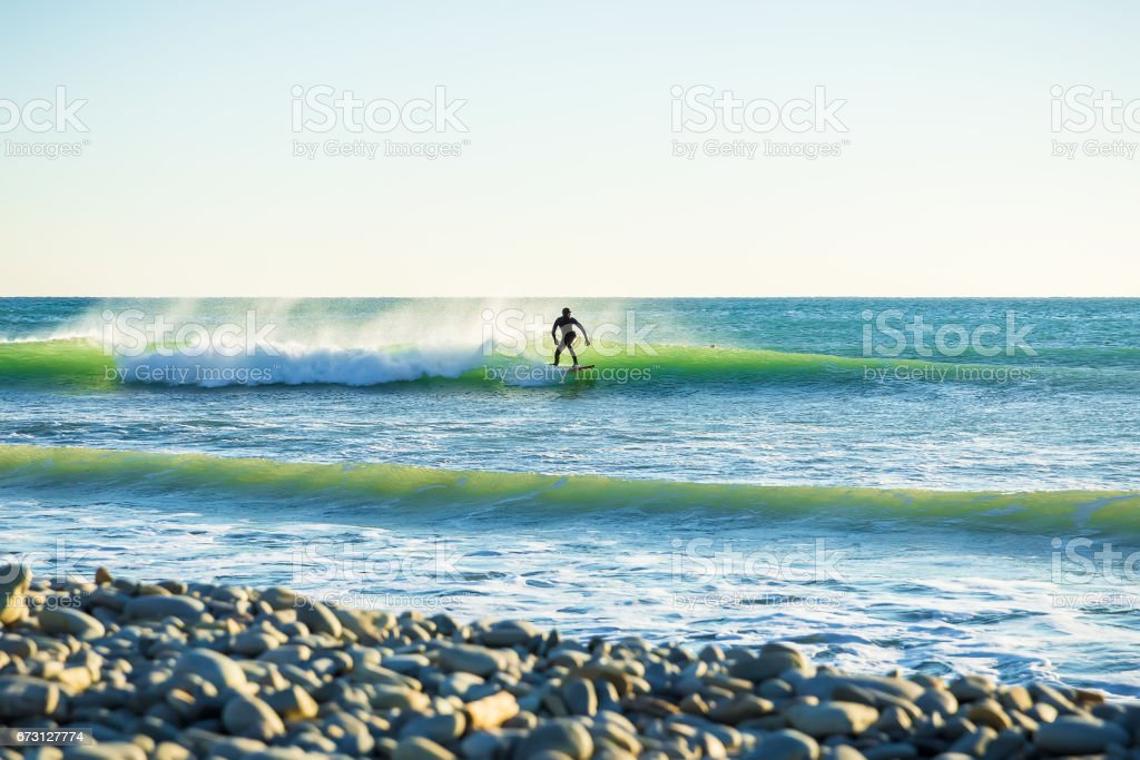 Surfing in the spring. Waves and surfer in ocean stock photo