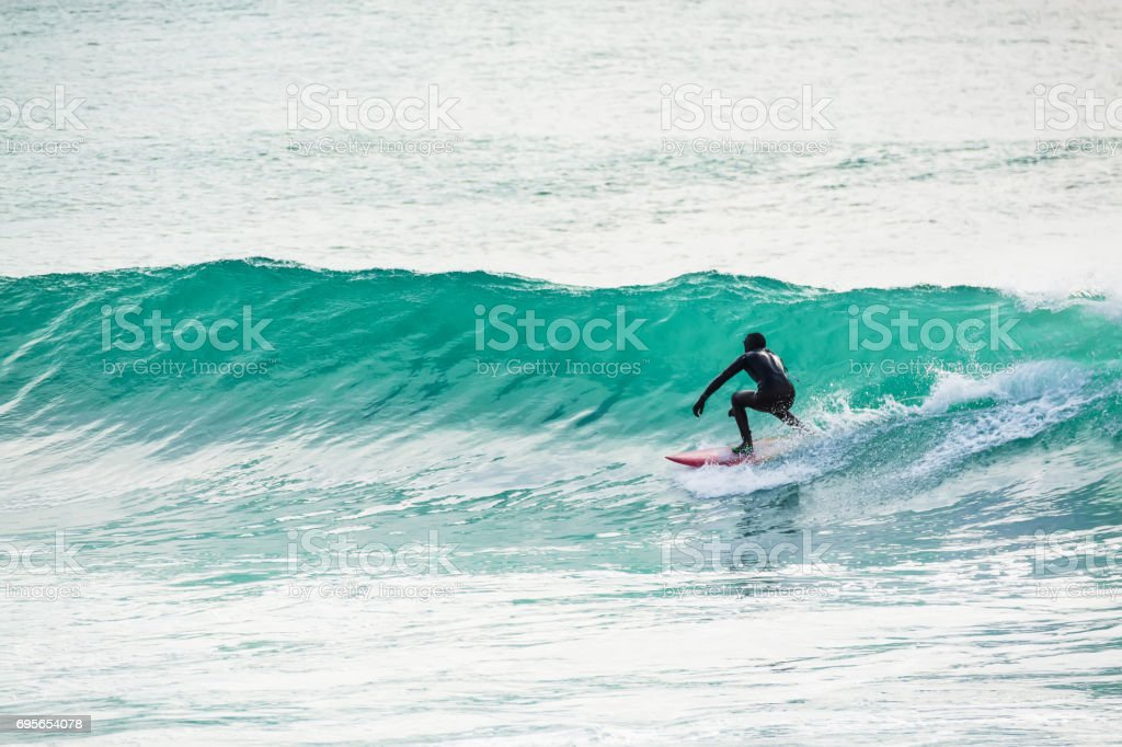 Surfing in turquoise barrel, wave in ocean. Surfer on wave stock photo