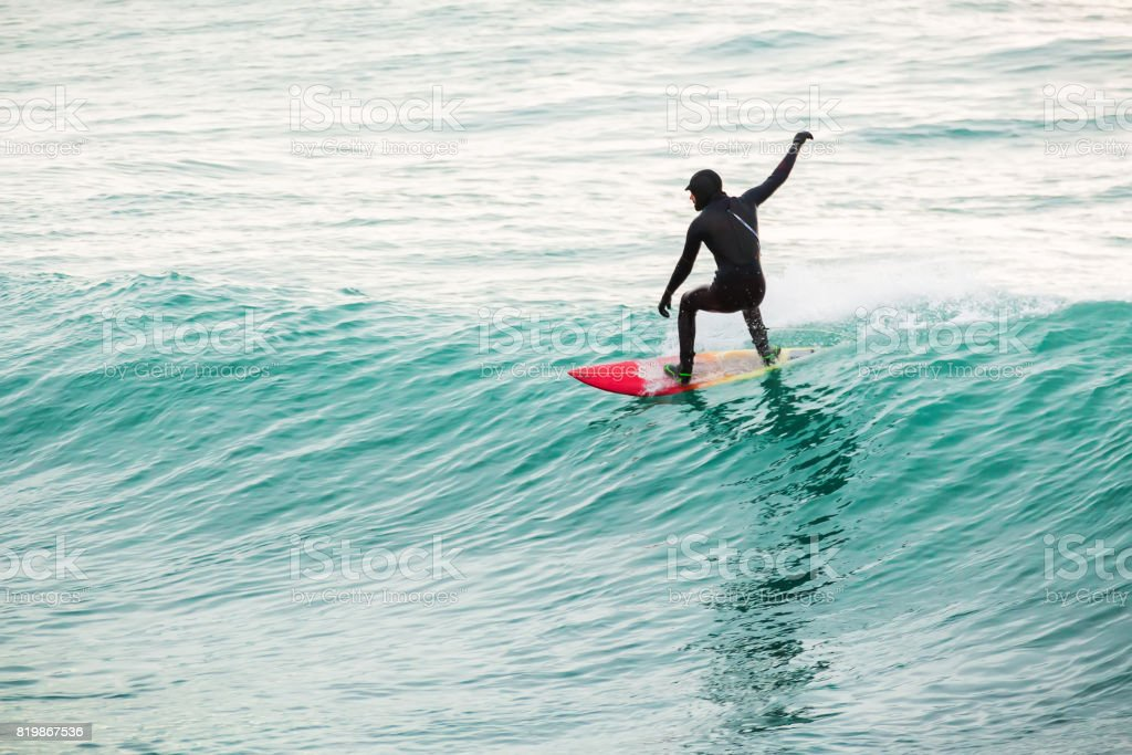 Surfing on turquoise wave in ocean stock photo