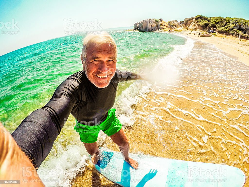 Surfing selfie of a senior man stock photo