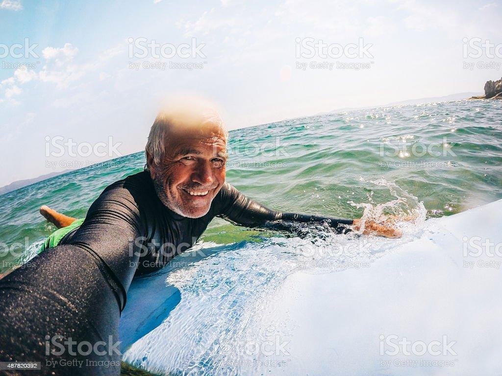Surfing selfie of a senior man stock photo