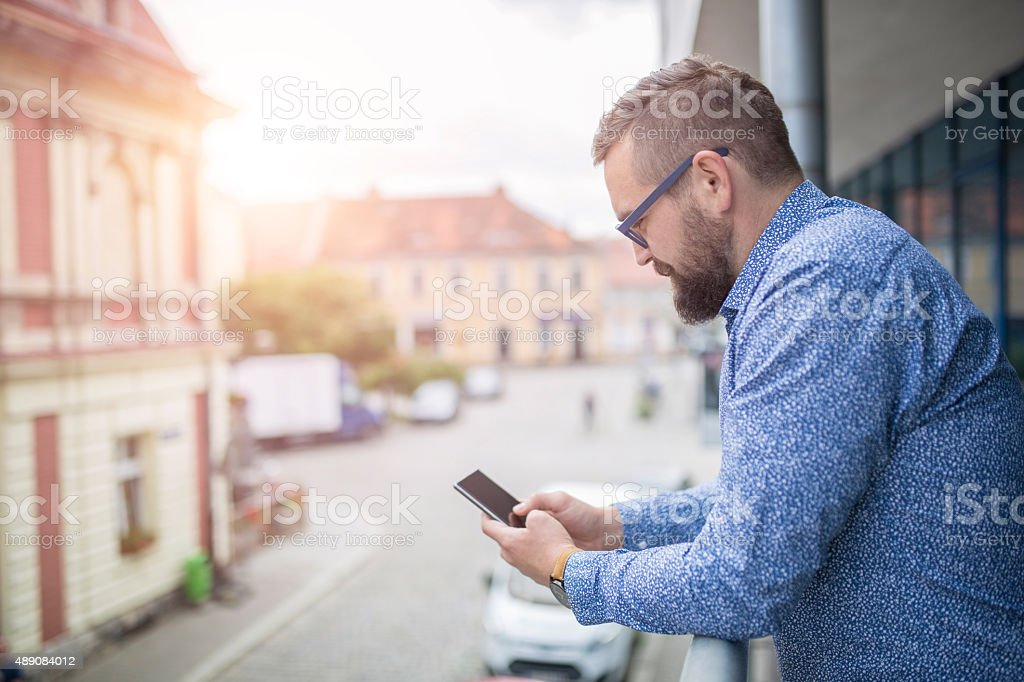 Surfing the net at terrace with city view stock photo