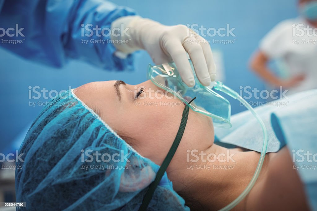 Surgeon adjusting oxygen mask on patient mouth in operation theater stock photo