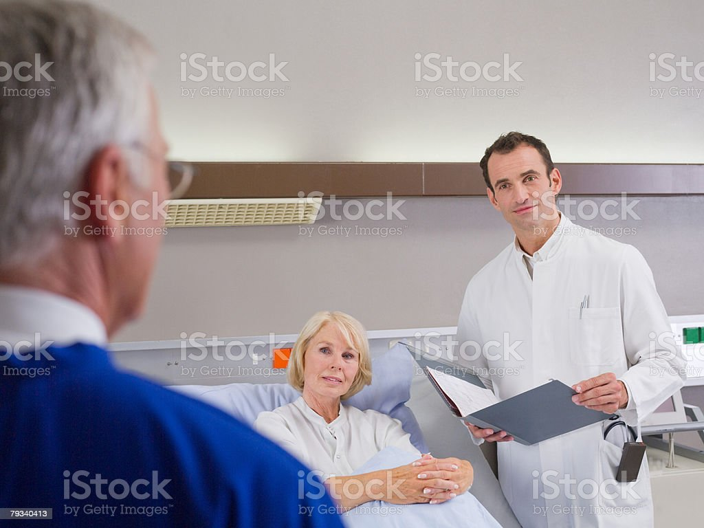 A surgeon and doctor with a patient stock photo