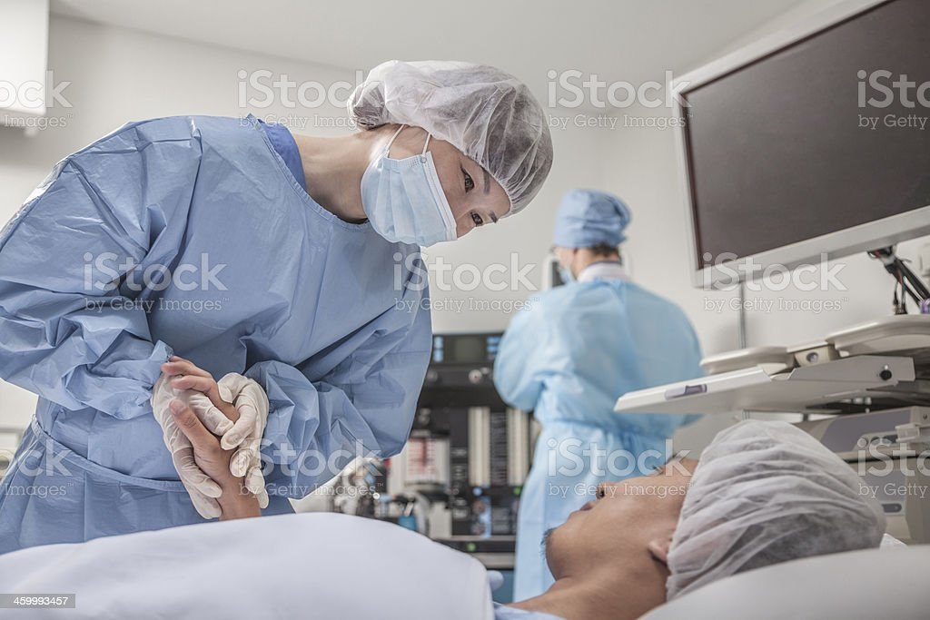 Surgeon consulting a patient, holding hands, getting ready for surgery stock photo