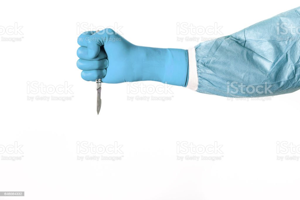 Surgeon fist in a latex glove on a white background is holding a scalpel to cut or stub stock photo