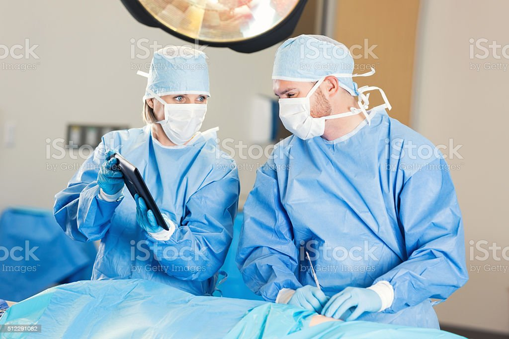 Surgeon uses digital technology during surgery stock photo