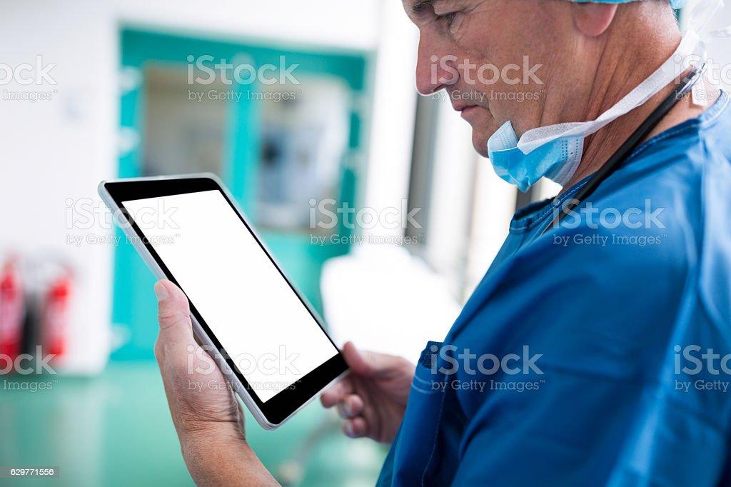 Surgeon using digital tablet in corridor stock photo