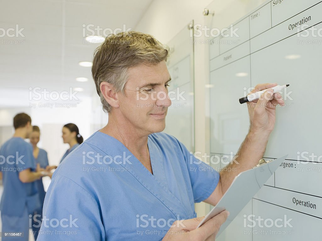 Surgeon writing on whiteboard royalty-free stock photo