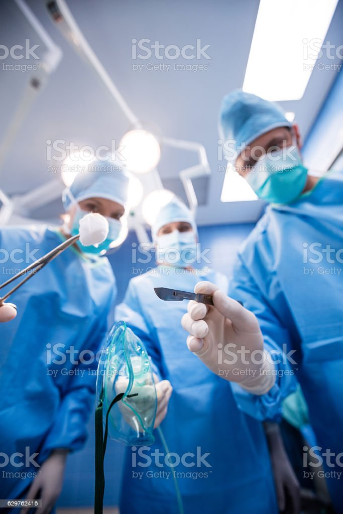 Surgeons holding surgical tools, cotton and oxygen mask stock photo