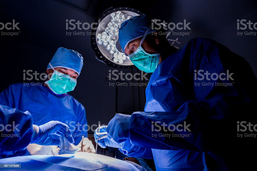 Surgeons performing complicated surgery on patient in operating room stock photo