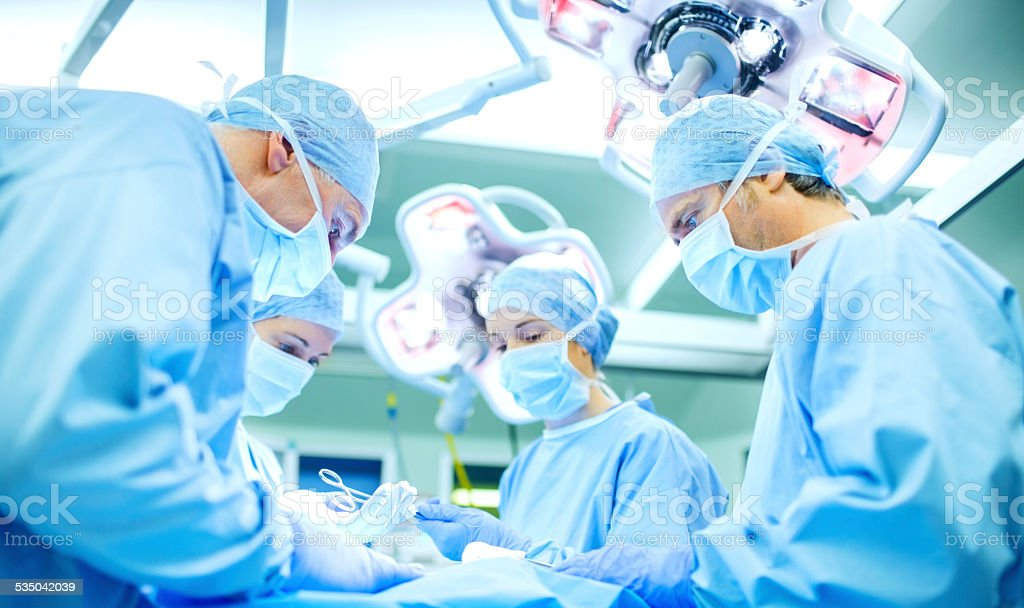 Surgeons Performing Surgery On Patient In Operating Room stock photo