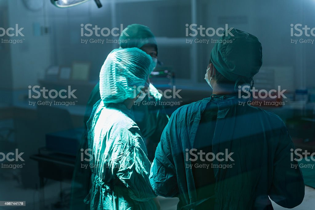 Surgery team speaking to each other at operating room stock photo