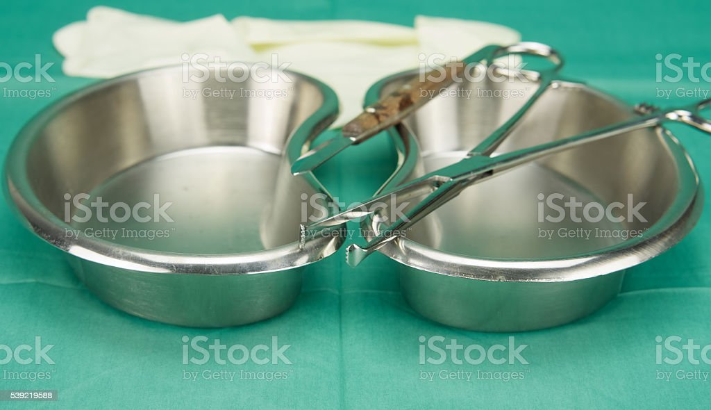 Surgical clamp and knife placed on stainless kidney shape bowl stock photo