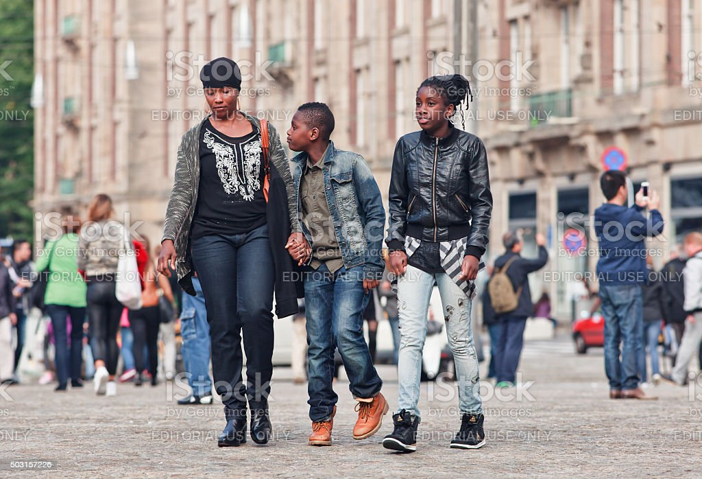 Suriname mother and children walking on Amsterdam Dam Square stock photo