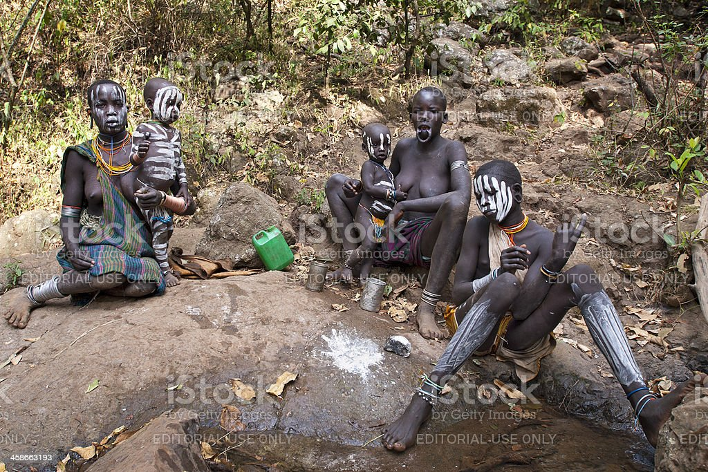 Surma women with children at water hole, Southern Ethiopia stock photo