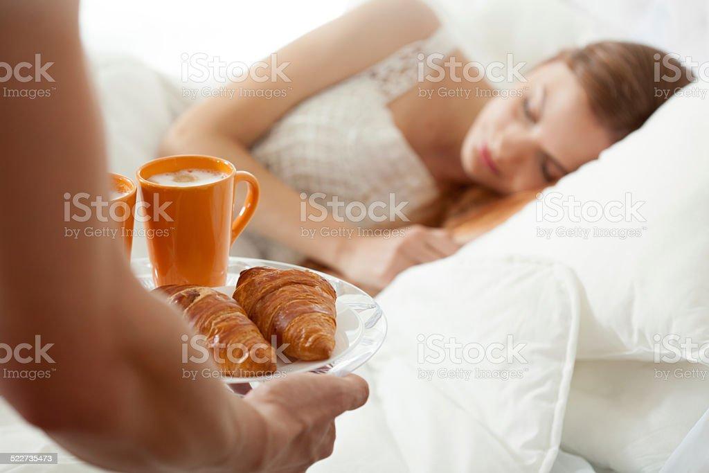 Surprise breakfast for sleeping woman stock photo