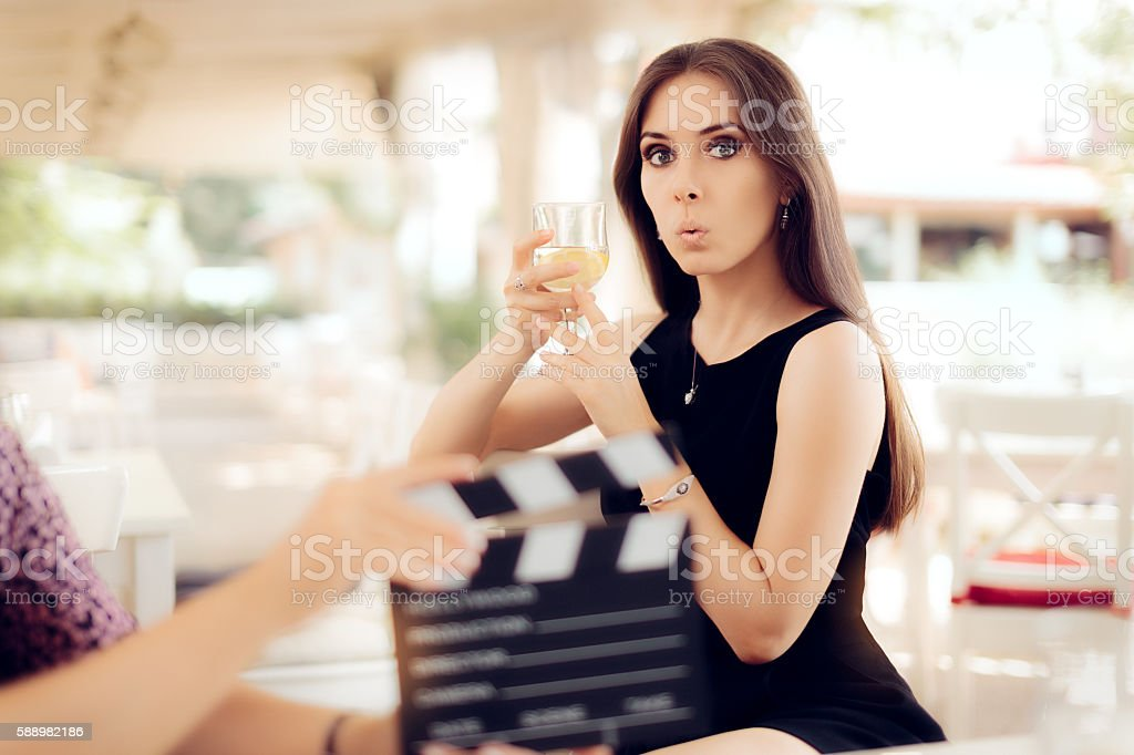 Surprised Actress Holding a Glass in Movie Scene stock photo
