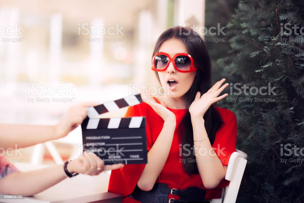 Surprised Actress with Oversized Sunglasses Shooting Movie Scene stock photo